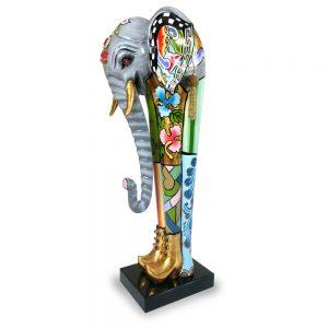 asugefallene elefanten skulptur mit buntem muster auf sockel, goldene stiefel