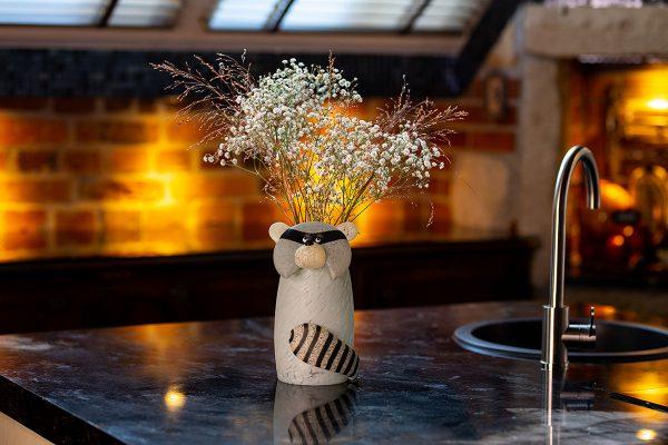 glasvase figur waschbär grau auf tisch mit blumen