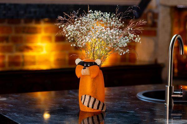 glasvase figur waschbär orange auf tisch mit blumen