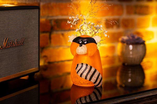 glasvase figur waschbär orange beleuchtet mit blumen