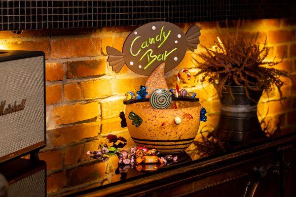 außergewöhliche glasschale für süßigkeiten bonbons auf holztisch bunt